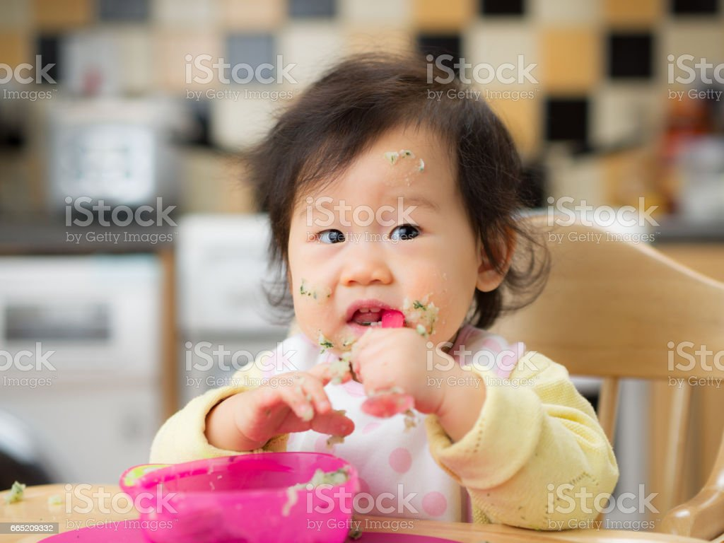 eating mess baby girl stock photo
