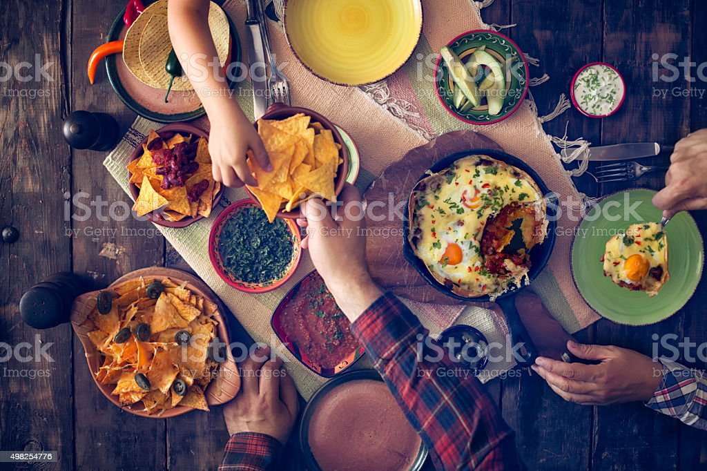 Eating Mexican Eggs and Tortilla Chips with Salsa and Jalapenos stock photo