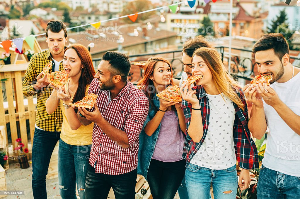 Eating pizza at a party on the roof stock photo