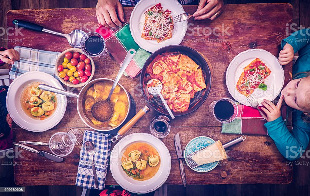 Eating Ravioli with Tomato and Tortellini Soup stock photo