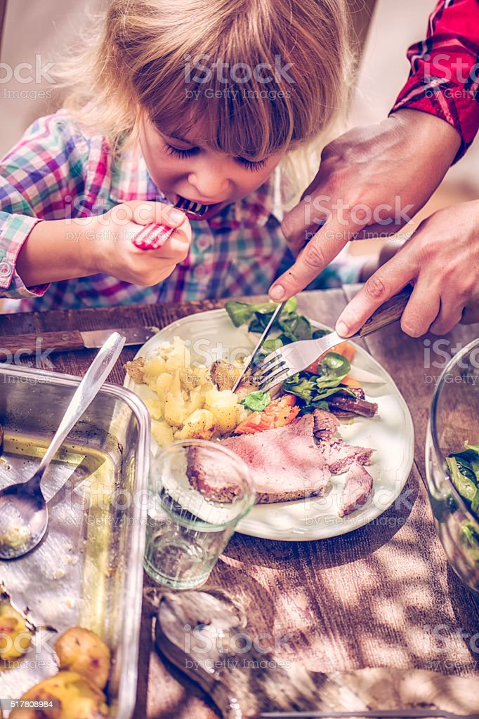 Eating Roast Beef with Potatoes and Root Vegetables stock photo