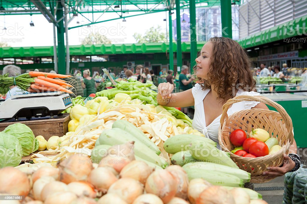 Eating Series: Young Woman Buying Carrots at Grocery Market stock photo