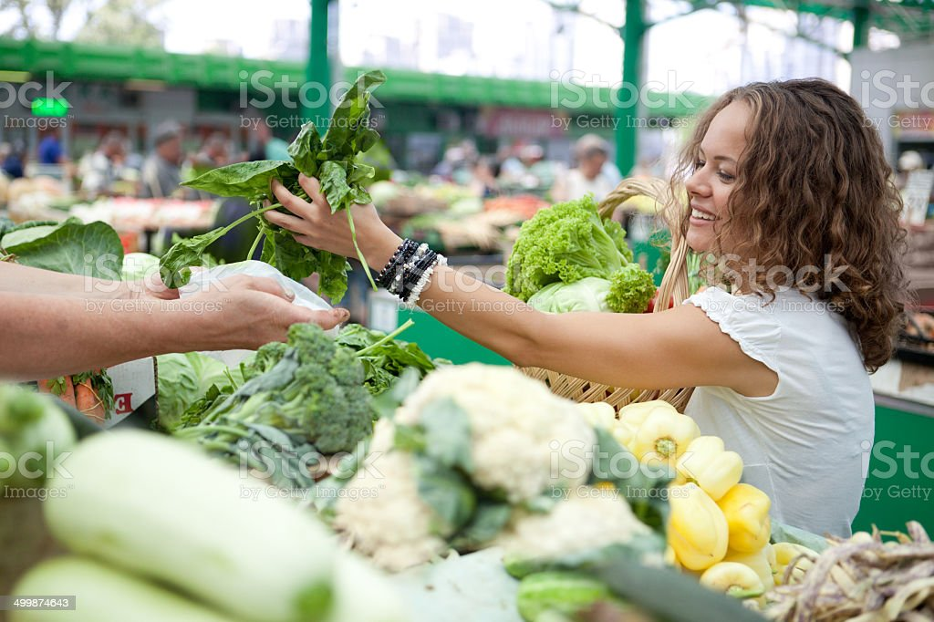 Eating Series: Young Woman Buying Spinach at Grocery Market . stock photo