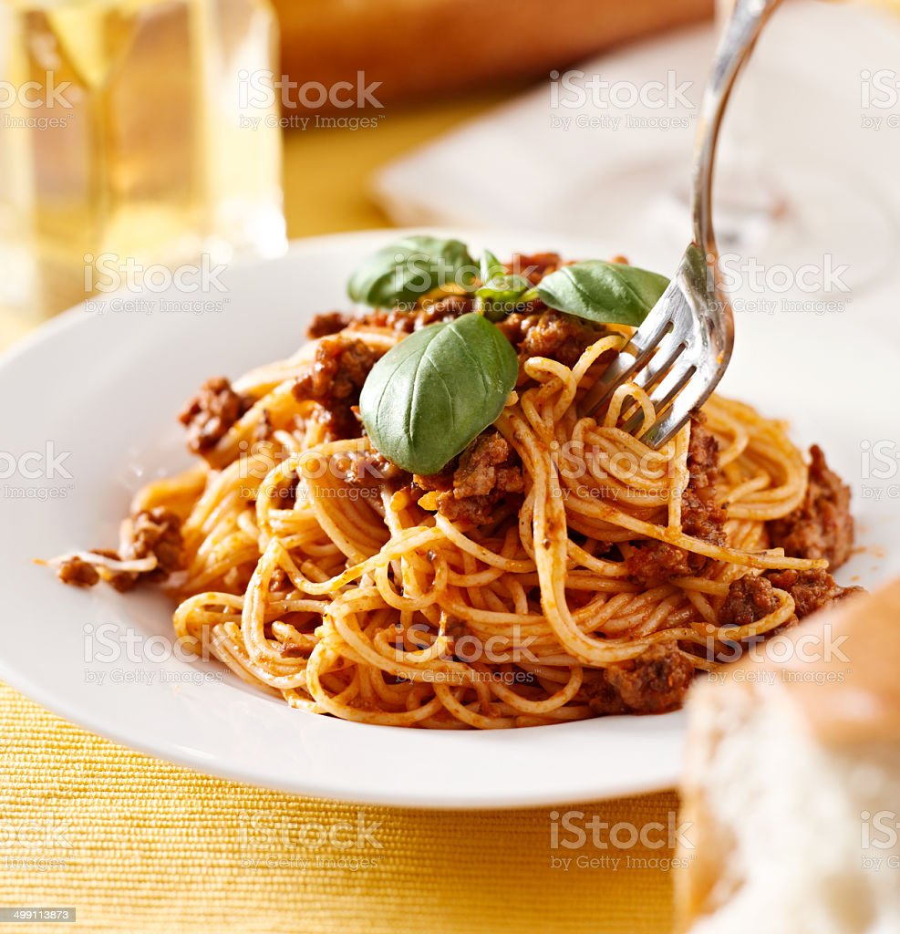 eating spaghetti with basil garnish in meat sauce stock photo