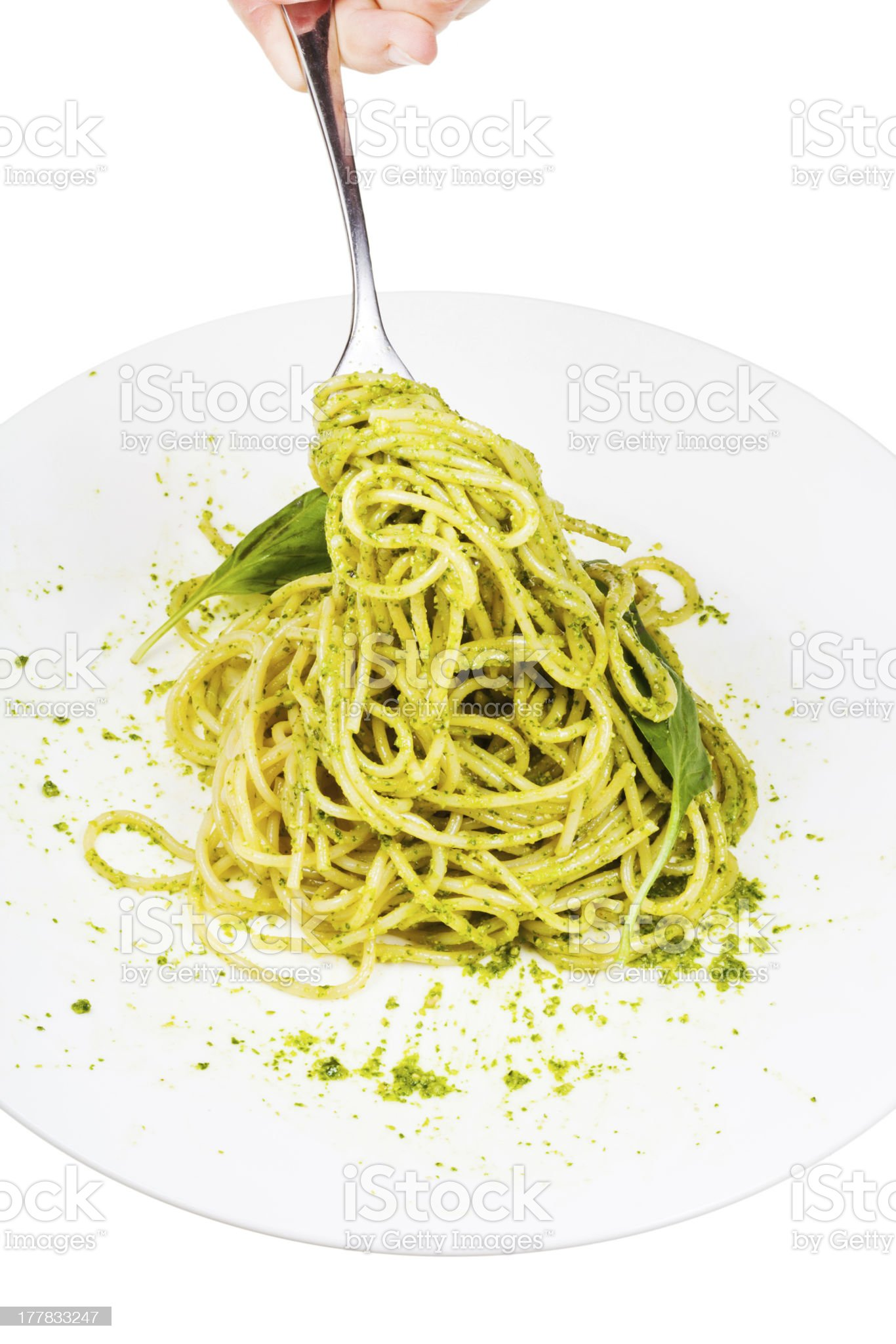 eating spaghetti with pesto isolated on white background royalty-free stock photo