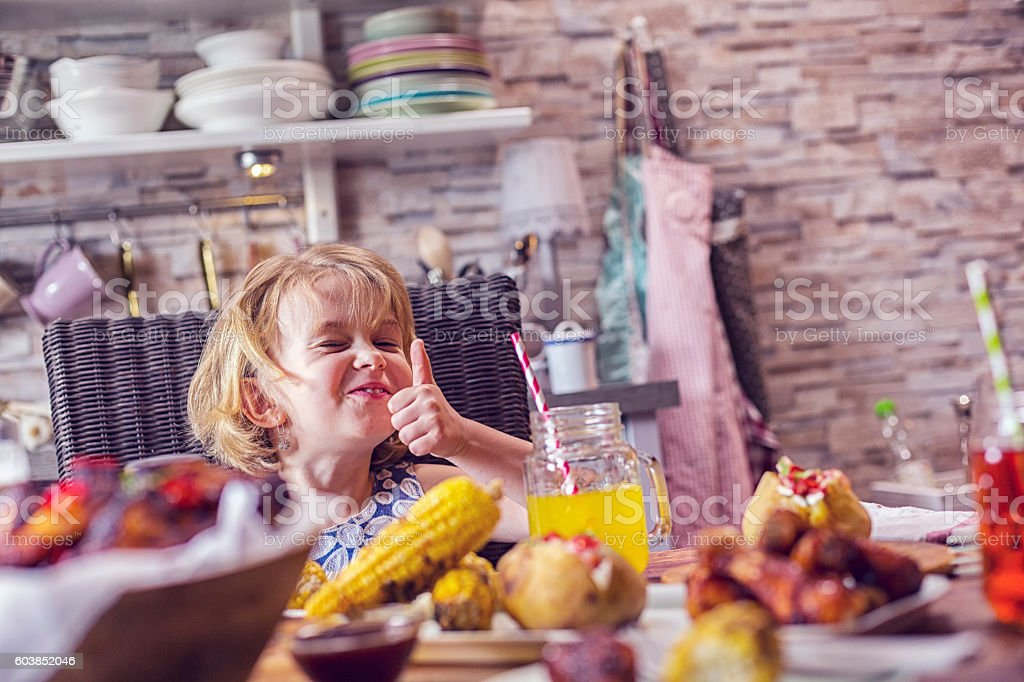 Eating Spicy Chicken Wings with Baked Potato and Corn stock photo
