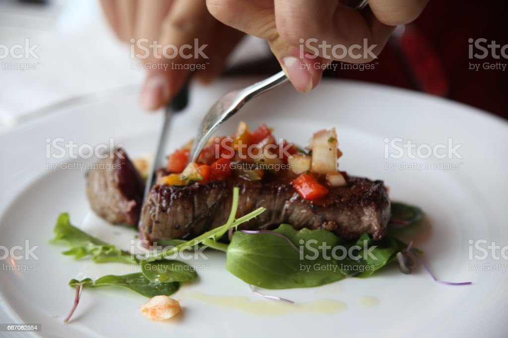 Eating steak with salad in a restaurant stock photo