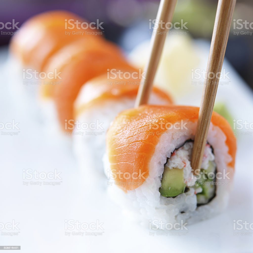 eating sushi with chopstricks stock photo