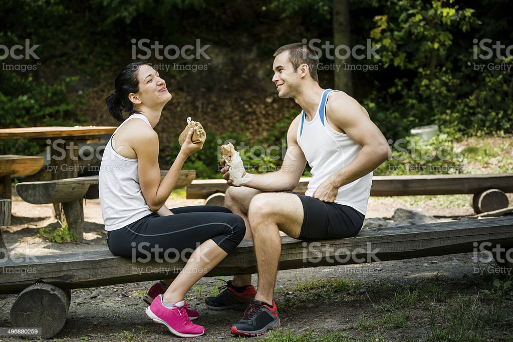 Eating together -  couple after sport training stock photo