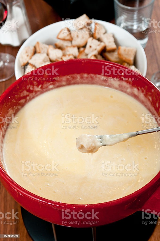 eating typical swiss cheese fondue stock photo