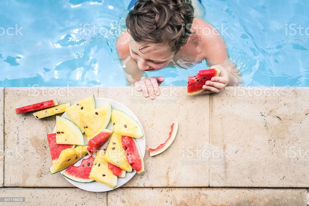 Eating watermelon in swimming pool stock photo