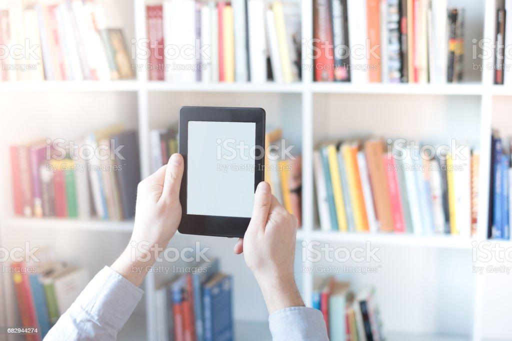 E-book reader in hands in a bookstore stock photo