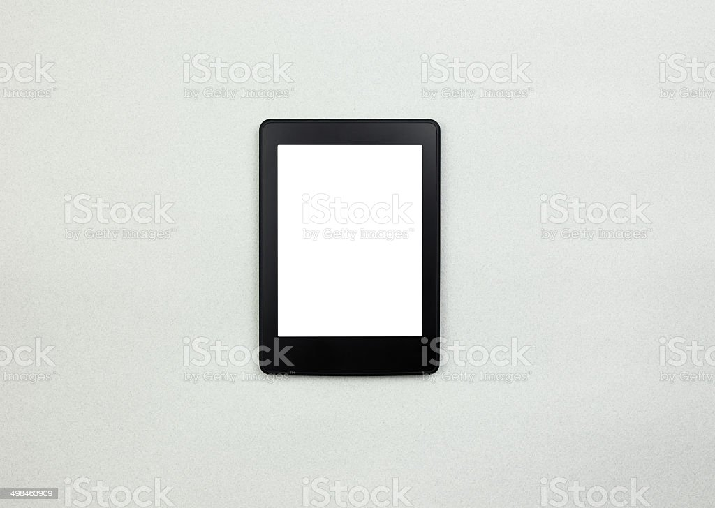 E-book reader or tablet pc on paper background stock photo