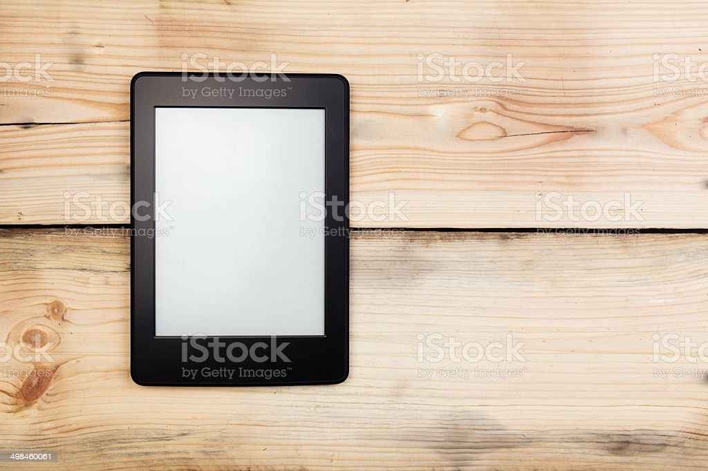 E-book reader or tablet pc on wooden background stock photo