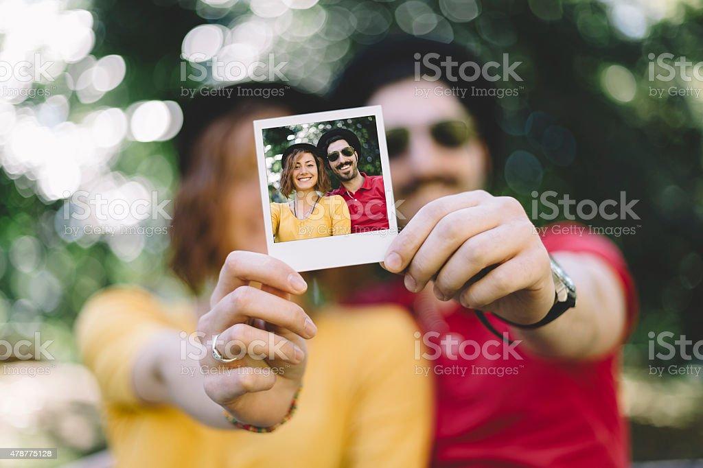 Eccentric couple holding a polaroid selfie stock photo