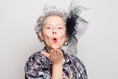 eccentric senior woman retro style blowing a kiss