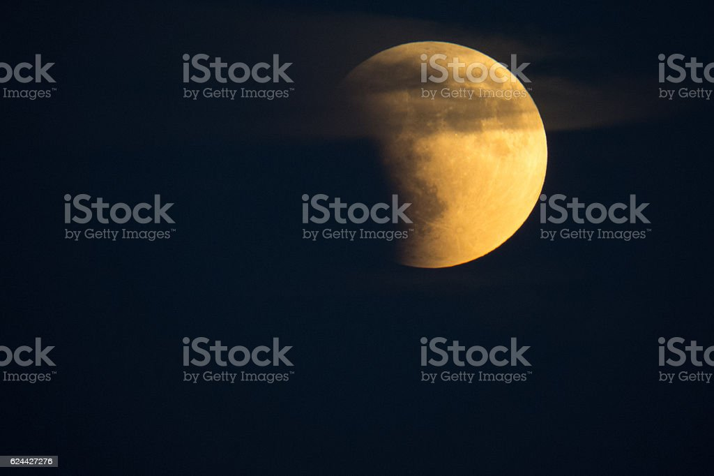 Eclipsing Moon with Cloud Halo stock photo