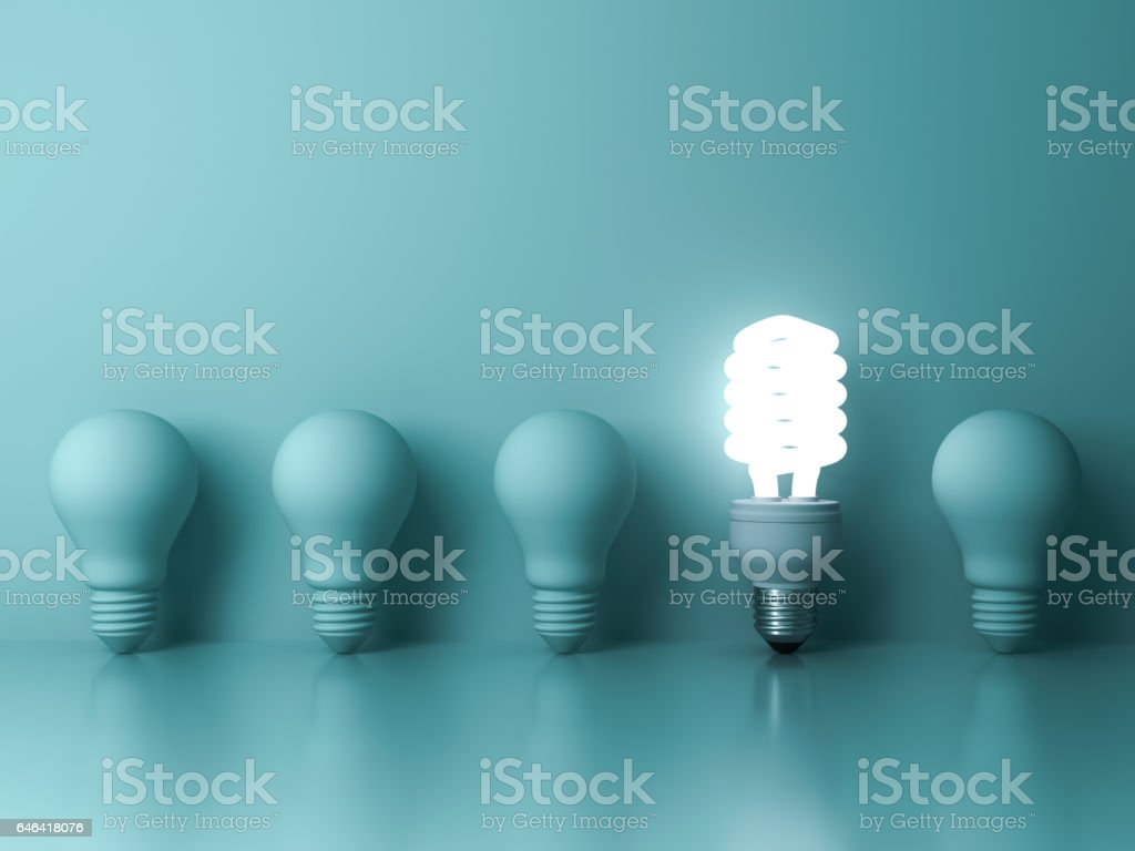 Eco energy saving light bulb , one glowing compact fluorescent lightbulb standing out from unlit incandescent bulbs reflection on green background stock photo