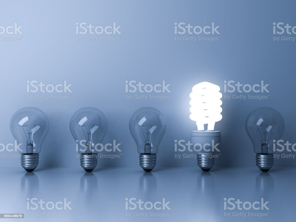 Eco energy saving light bulb , one glowing fluorescent lightbulb standing out from unlit incandescent bulbs reflection on blue background , individuality and different ideas concepts 3D rendering stock photo