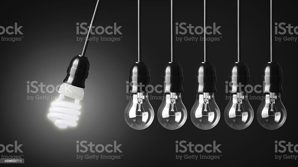 Eco friendly light bulb with row of Edison light bulbs stock photo