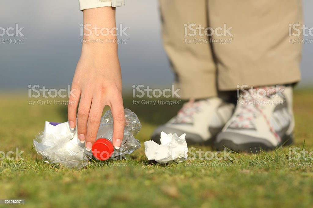 Eco hiker hand collecting garbage in the mountain stock photo