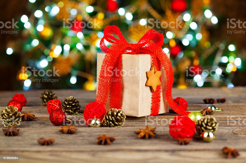 Eco holiday gift on rustic wood table infront Christmas tree stock photo