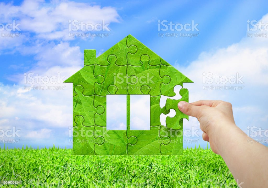 Eco house concept, hand build house from puzzle stock photo