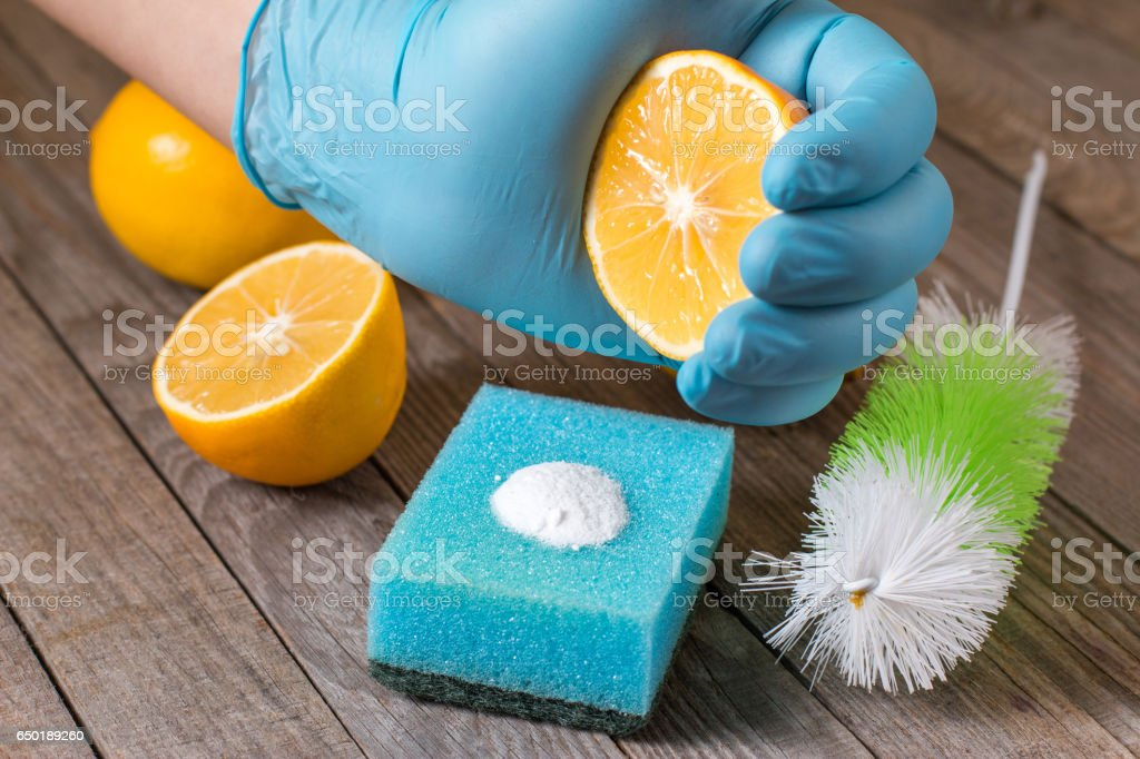 Eco-friendly natural cleaners baking soda, lemon and cloth on wooden table in hand on wooden table stock photo