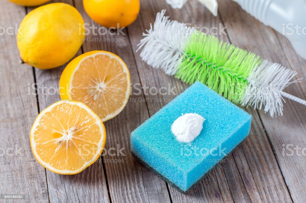 Eco-friendly natural cleaners baking soda, lemon and cloth on wooden table Homemade green cleaning stock photo
