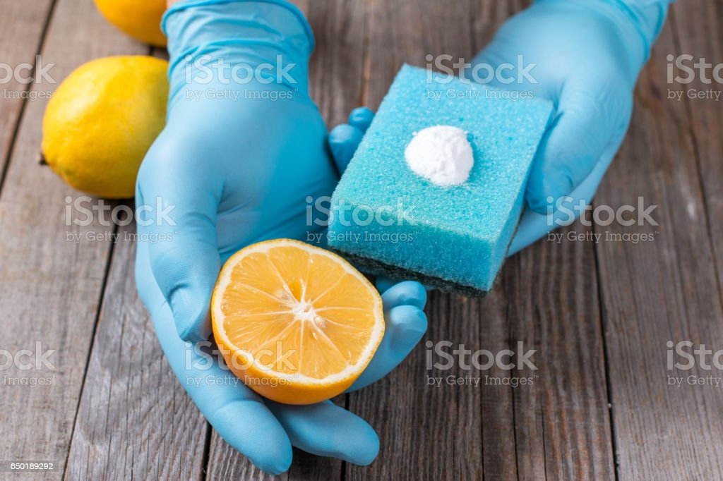 Eco-friendly natural cleaners in hand on wooden table stock photo