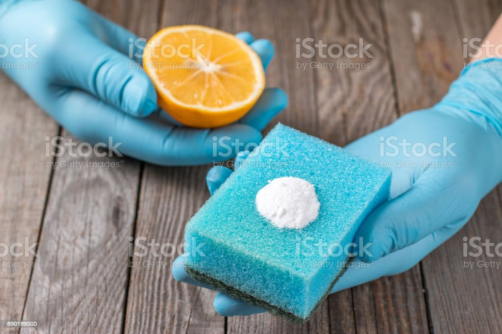 Eco-friendly natural cleaners lemon, baking soda and cloth on wooden table in hand on wooden table stock photo
