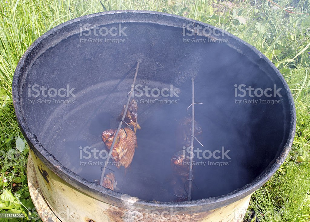 Ecologic fish smoke in smokehouse rusty barrel royalty-free stock photo