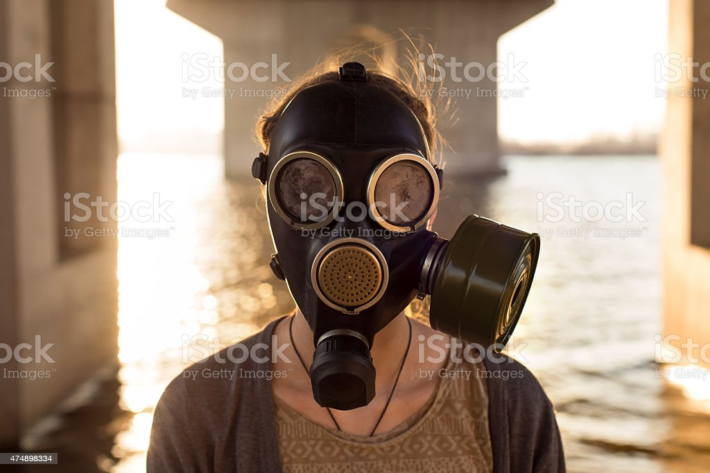 Ecological concept of air contamination. Woman in gas mask stock photo