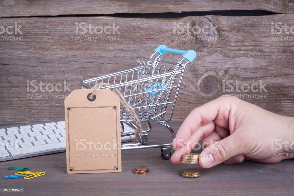 E-commerce concept. Purchasing cart with a blank price tag on a dark wooden background stock photo