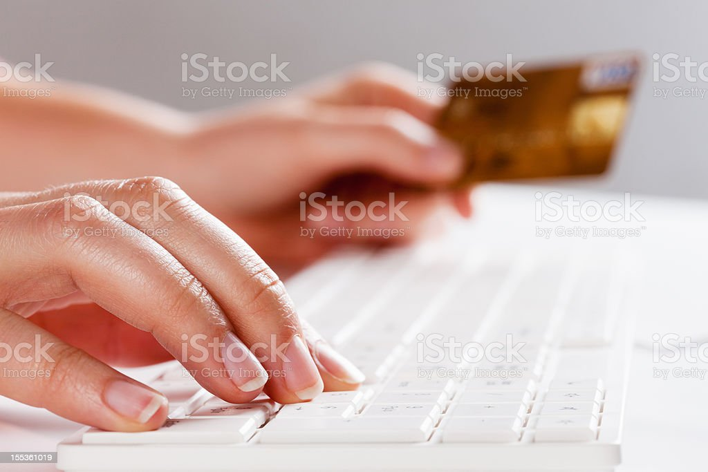 E-commerce: hands with credit card type on computer keyboard stock photo
