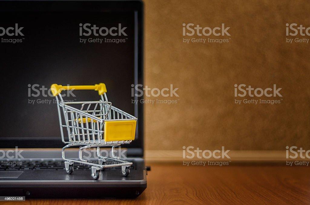 E-commerce. Shopping cart on laptop. Conceptual image stock photo
