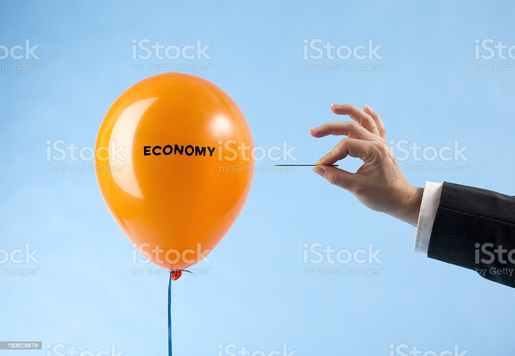 'Economy' balloon attacked by hand with needle stock photo