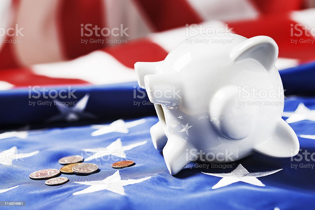 US economy: fallen piggy bank and flag royalty-free stock photo