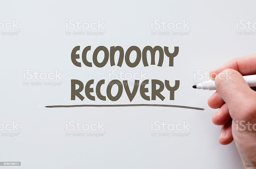 Economy recovery written on whiteboard stock photo