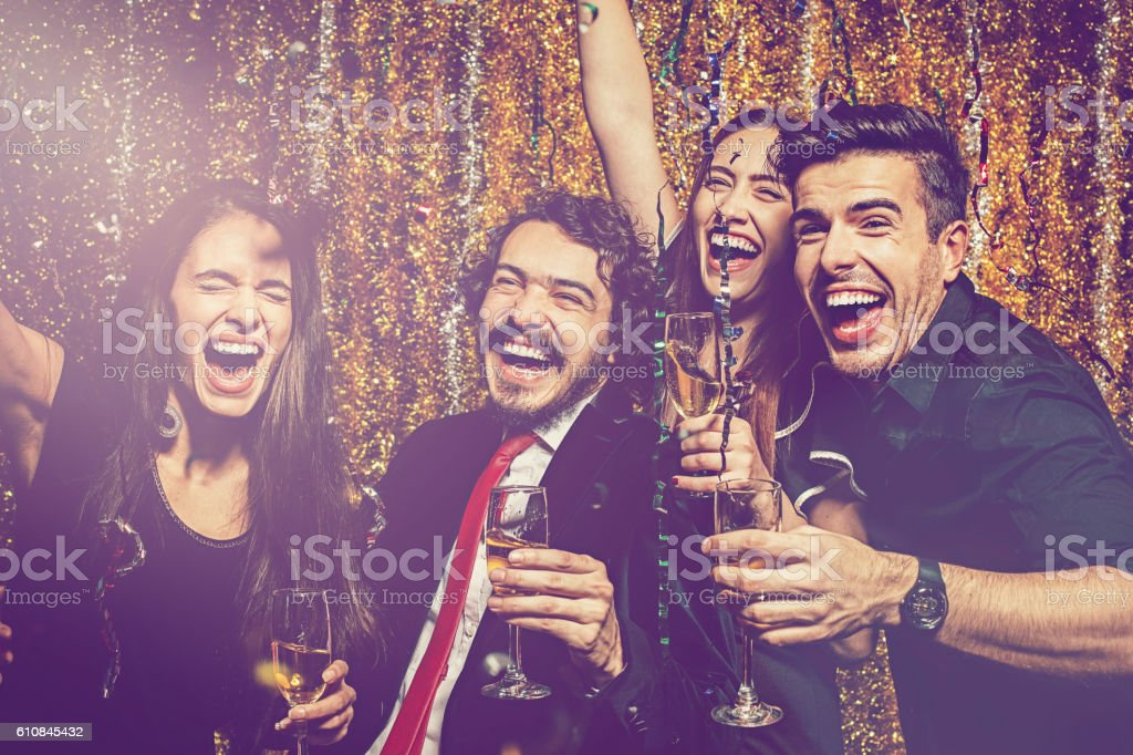 Group of cheerful people holding champagne glasses shouting at New...