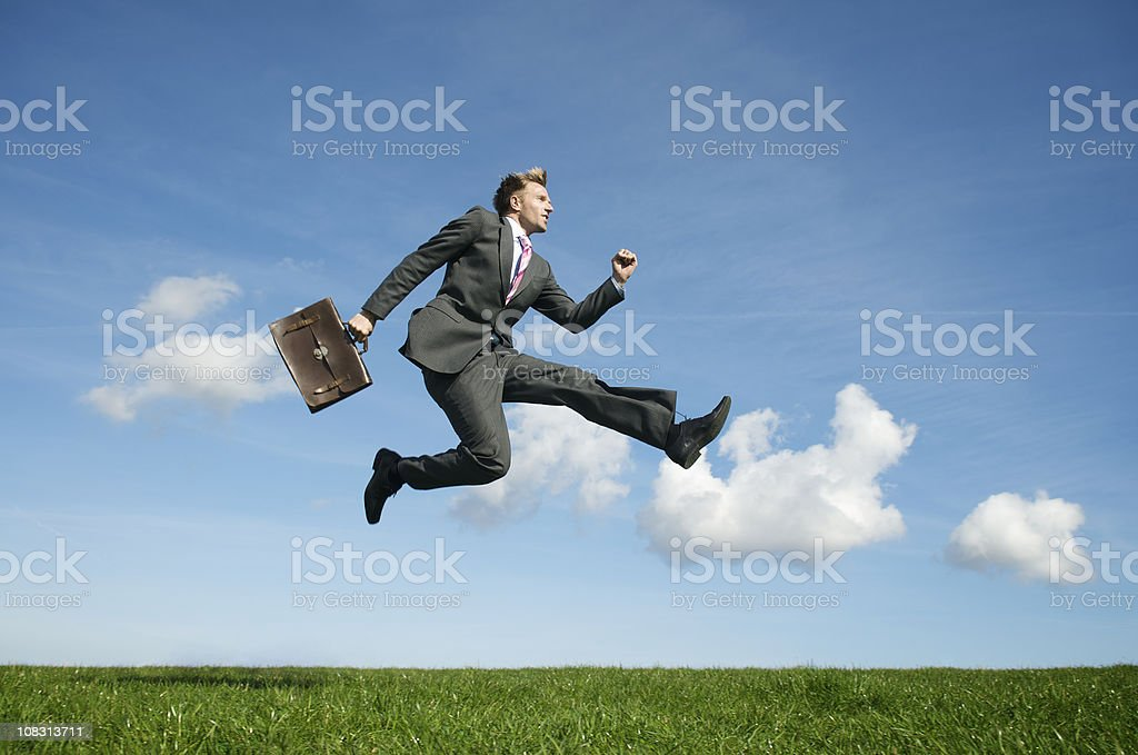 Ecstatic Businessman Jumping Outdoors in Blue Sky Green Field royalty-free stock photo