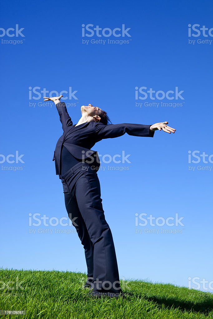 ecstatic businesswoman arms outstretched on green grass royalty-free stock photo