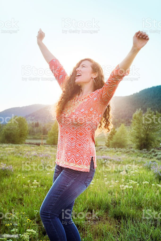 Ecstatic excited young woman hollers in nature stock photo