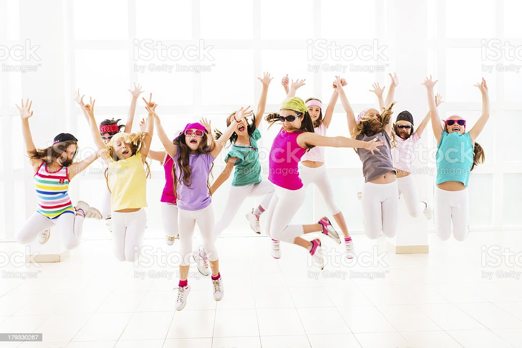 Large group of ecstatic little hip hop dancers jumping in a dance...