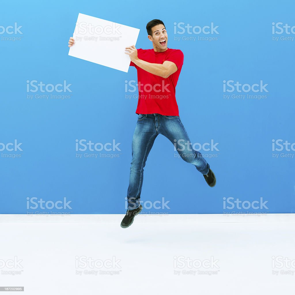Ecstatic man jumping with a white placard royalty-free stock photo