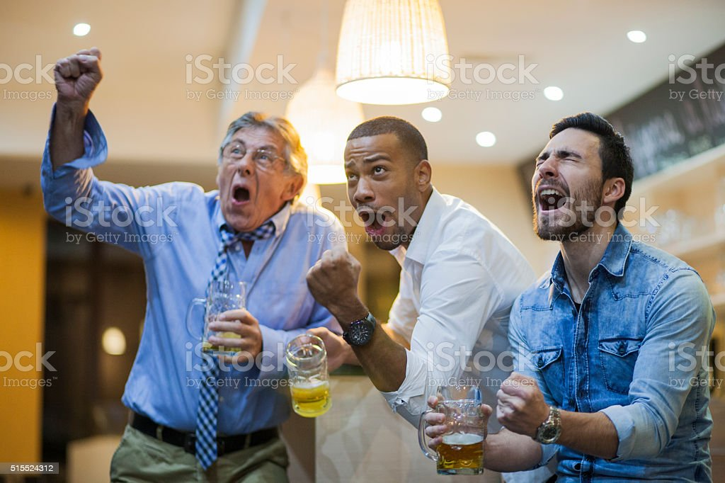 Ecstatic men watching soocer game in a bar after work stock photo