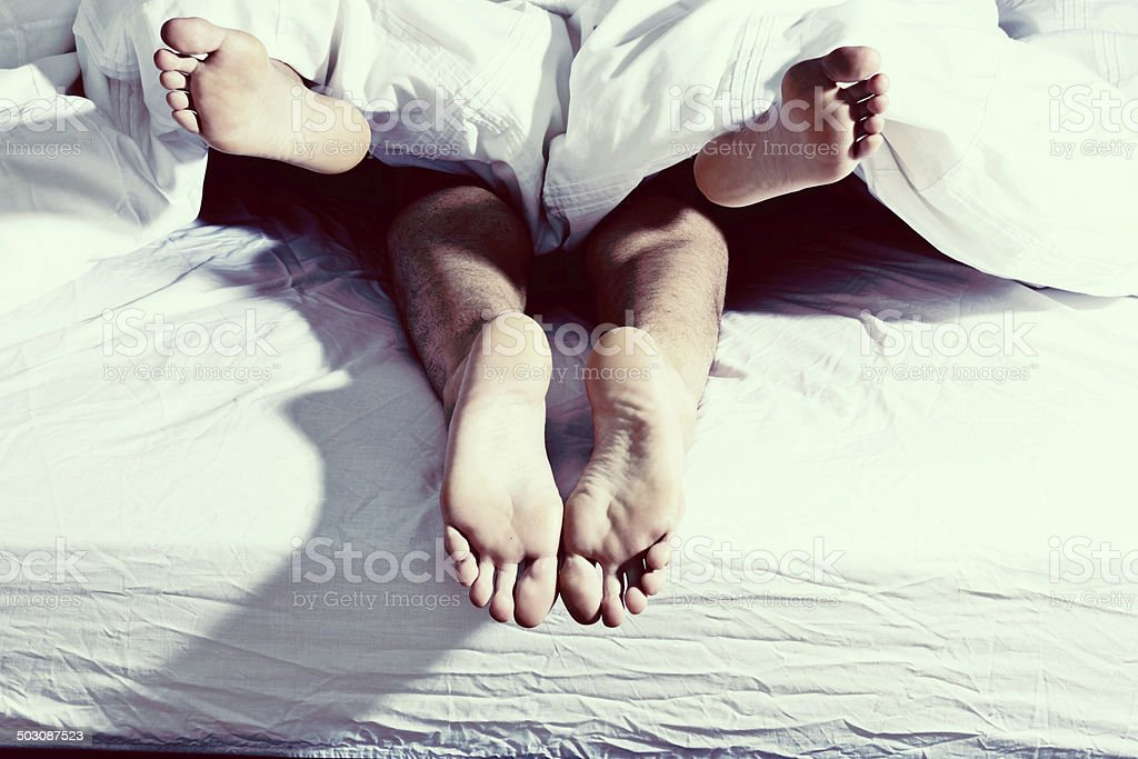 The feet of an anonymous couple reaching a moment of ecstasy as they...