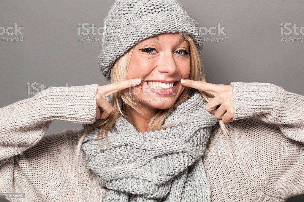 ecstatic sexy 20s winter girl expressing joy with fake smile stock photo