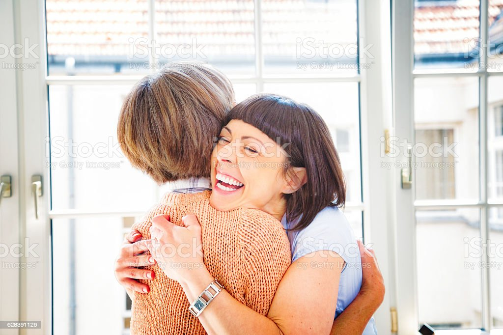 Ecstatic woman hugs her senior mother with a big smile stock photo