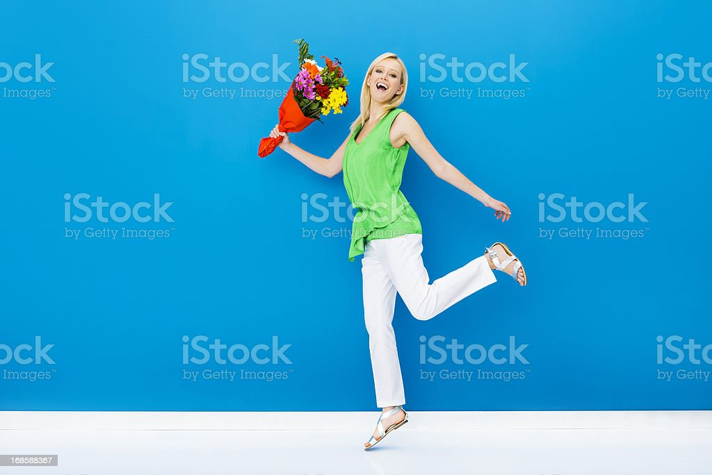 Ecstatic woman jumping with a bunch of flowers royalty-free stock photo